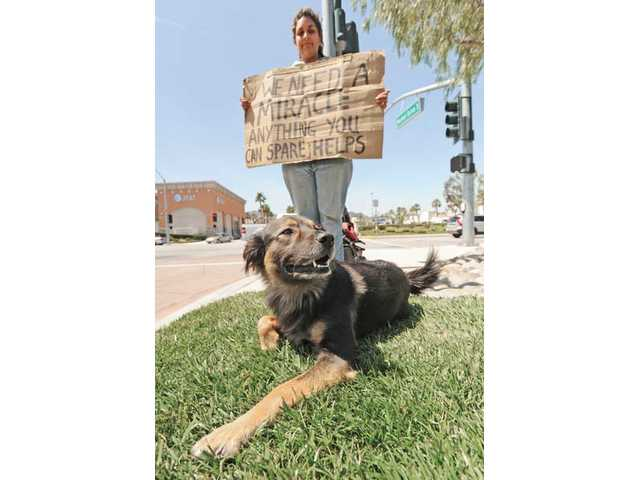 Sarah Stewart and Moogassa stand with a sign asking for a miracle. Due to medical bills, the couple has been left homeless, asking for money to get to Jeff Stewart's doctor in Woodland Hills on Thursday.