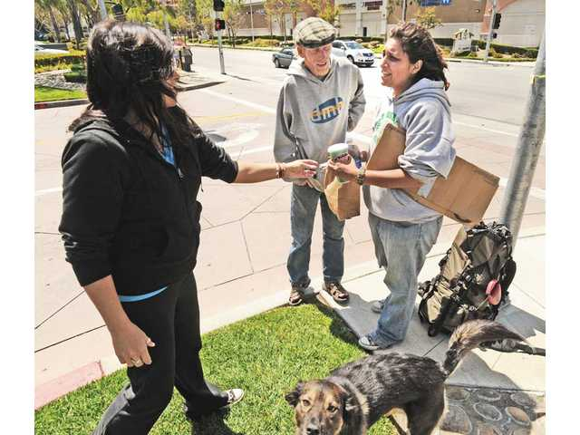 A Stevenson Ranch resident, left, hands a sandwich and cash to Jeff Stewart, 37, and his wife, Sarah, 25, of Livermore, as they stand with their dog Moogassa on The Old Road near Pico Canyon Road in Stevenson Ranch on Thursday.