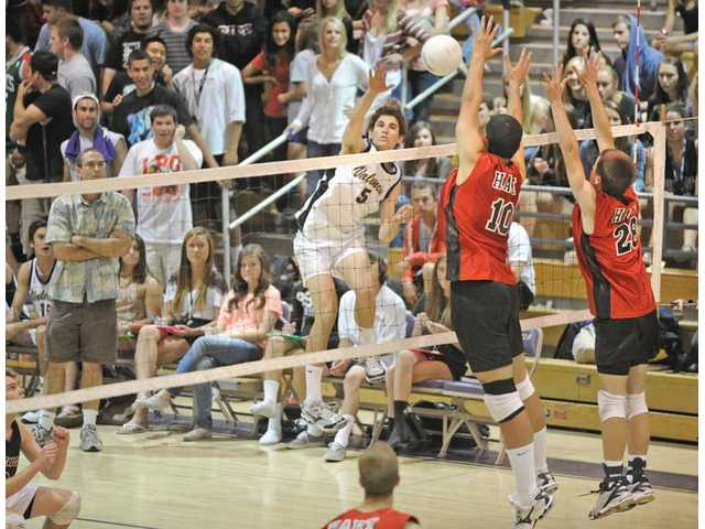 Valencia's Kurt Fults (5) spikes the ball on Thursday at Valencia High as Hart's Taylor Gregory (10) and Chris Leclair (28)  try to block. Valencia won the match, its 96th consecutive league victory, tying a state record.