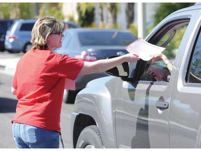 Fair Oaks Ranch Community School teacher Danielle Paroda hands out literature explaining buget cuts at the school to parents picking up their kids in Canyon Country on Friday. About one-third of the school's 34 teachers received preliminary layoff notices.