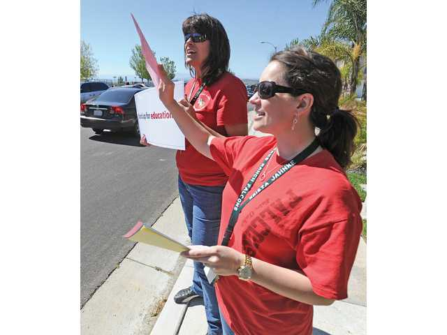 Fair Oaks Ranch Community School teachers Lauri Reddick, left, and Krista Jahne hand out literature explaining budget cuts at their school to parents picking up their kids in Canyon Country on Friday.