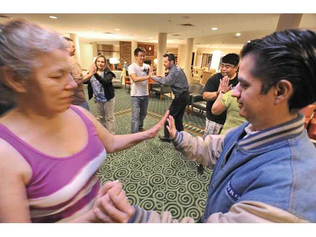 Josie Mead, left, and Carlos Hernandez, right, practice dancing with their class in the Rueda de Casino style of Cuban style salsa dance at The Courtyard Marriott in Valencia.