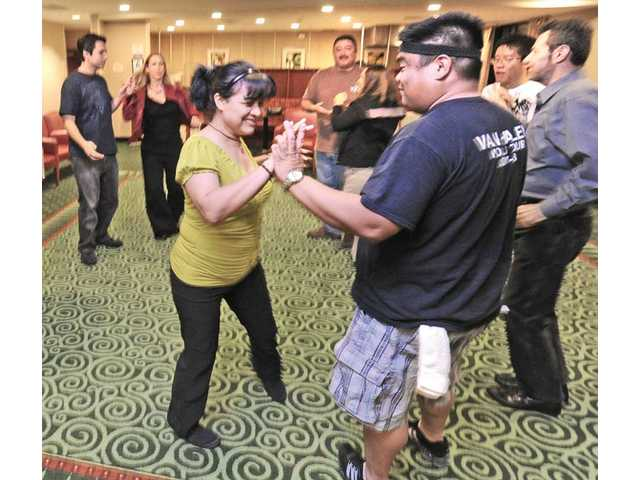 Salsa instructor Aries Alegado, right, teaches a new move to Amanda Arevalo, of Saugus.