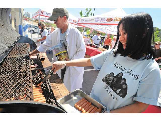 Volunteers Susie Liem, right, and Joe Ferrara grill hot dogs and hamburgers at the Arakaki Family Fundraiser and Classic Car Show held in the Albertsons parking lot in Saugus on Saturday.