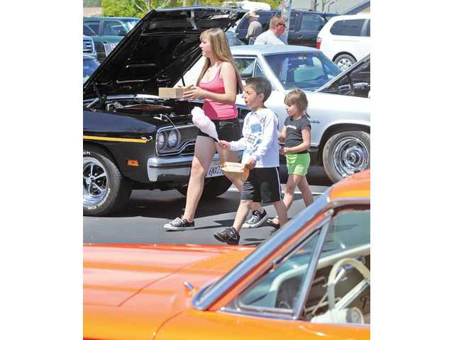 Samantha Bell 14, left, Kai Giglio, 8, and Bella Giglio, 5, walk among the classic cars on display as they sell popcorn and cotton candy at the fundraiser.