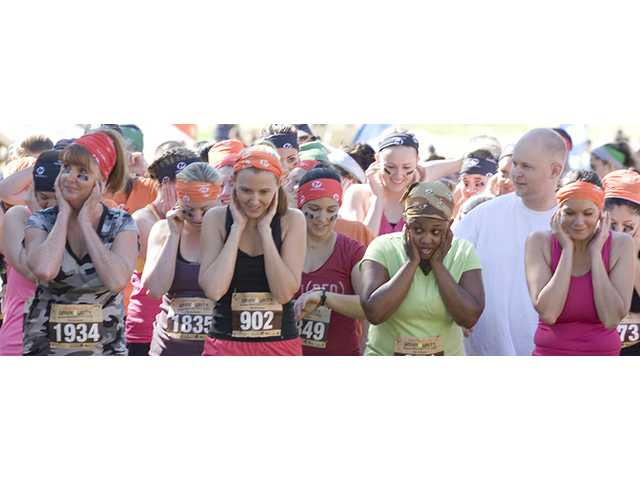 Participants cover their ears before the starting gun fires at the beginning of the 5-kilometer race.