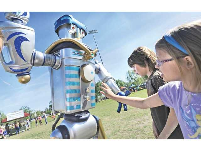 Luciano Verga, 8, center, and Calla Coulter, 5, touch a robot made of recycled materials by local artist Dave Barron at the City of Santa Clarita Earth Arbor Day Festival event held at Central Park in Saugus on Saturday.