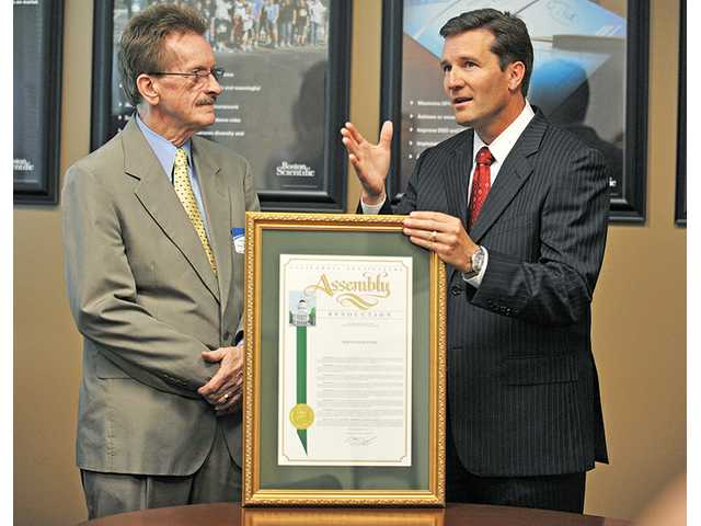 Michael Onuscheck, president of Boston Scientific, right, expresses his gratitude at the company's offices in Valencia on Monday after his company receives recognition from  the state Assembly via Paul Strickland, left, a field representative for Assemblyman Cameron Smyth, R-Santa Clarita.