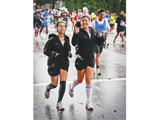 Academy of the Canyons students Jazmin Gonzalez and Carolyn Thio run on Rodeo Drive during the recent 26.2-mile Los Angeles Marathon. Nearly 20 local high school students ran the marathon after training with Students Off And Running, a division of the Santa Clarita Track Club.