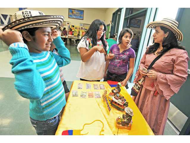 From left, Roxana Luna, 9, tries on a caña flecha, a handmade straw hat, as Lisette Hernandez, 10, and Elena Castillo, 9, talk to Rebeca Alvarez about crafts and culture from Colombia.