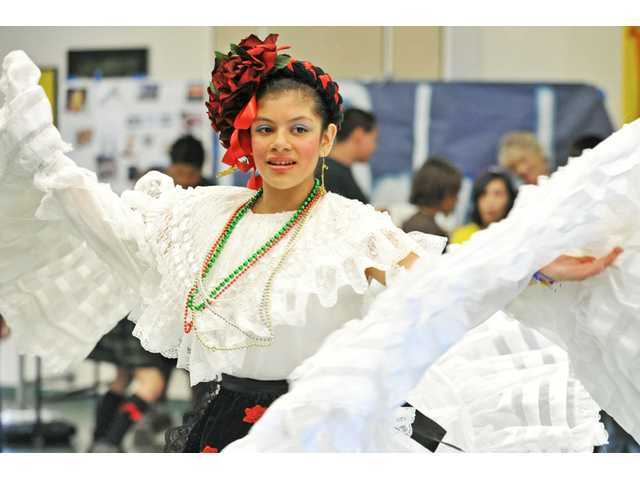 "Seventh-grader Tiffany Ocampo, 12, performs a traditional Mexican folklórico dance to the tune of ""Morena De Mi Corazón"" during Journey Around The World, Leona Cox Community School's multicultural day event, at the Canyon Country school on Tuesday."