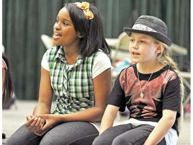Amani Rasheed, left, and Elle Schroeder sing along as the cast rehearses.