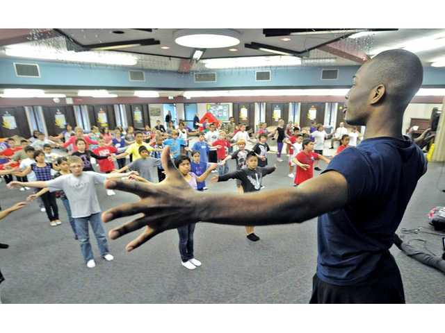 Dance assistant Michael Battle, right, leads a group of some 80 fifth-graders in warm-up exercises as the students prepare to practice.