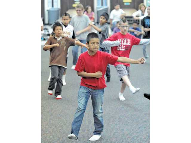 Adrian Gonzalez, 10, front, join his fifth-grade classmates as they perform a dance number at the end of their 12-week dance class.