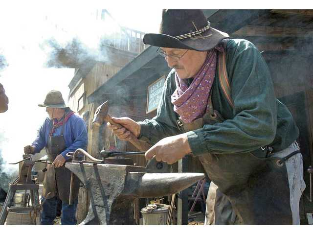 Wishbone McCreay, right, and Ryan Jones customize horseshoes for visitors during last year's festival.