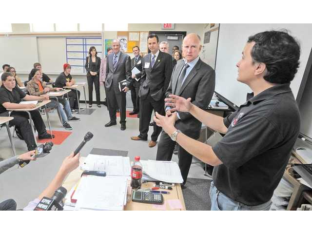 Chemistry teacher Brandon Duran, right, dicusses the challanges he faces in the classroom due to budget cuts with Gov. Jerry Brown, center, as Brown tours a class of 10th- through 12th-grade chemistry students at Hart High School in Newhall on Thursday.