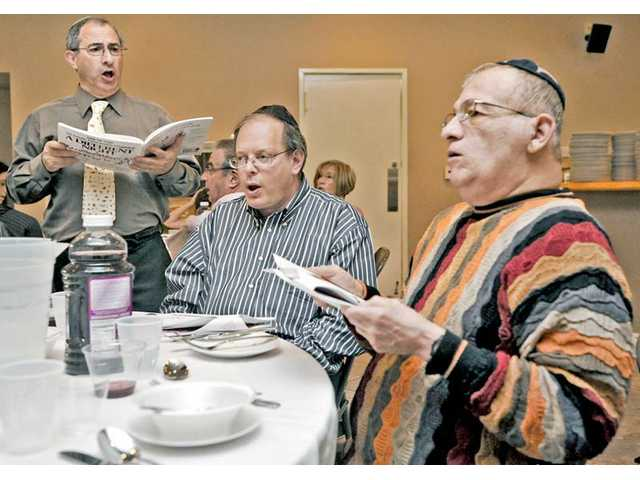 "From left, Cantor Kenny Ellis, leads a singing of the American Negro spiritual ""Go Down Moses"" as Arnold Gelb of Corte Madera and Al Ponce follow along as part of the Passover service hosted by Temple Beth Ami."