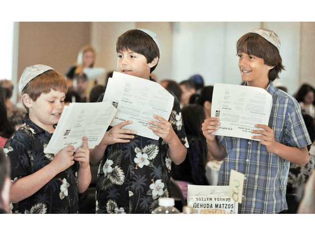 From left, Philip Stulman, 9; his brother Sam Stulman, 11; and Max Cogan, 11, recite the Four Questions during the Seder dinner as part of the Passover service hosted by Temple Beth Ami at the Valencia Hills clubhouse in Valencia on Tuesday.