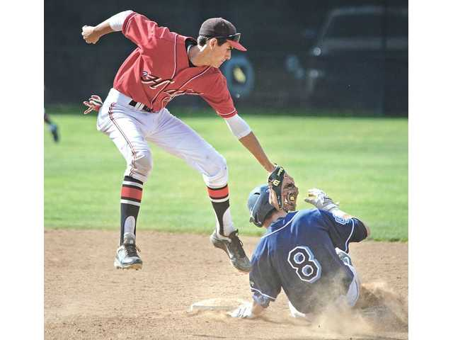 Saugus' Connor Wilson (8) slides under the tag of Hart's Luke Persico on Friday at Hart High School.
