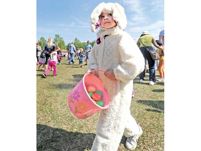 Josie Regez, 4, of Canyon Country, wears a handmade Easter-bunny suit, as she looks for her parents after filling her basket with prize-filled plastic eggs at the Santa Clarita-sponsored Eggstravaganza Easter egg hunt at Central Park in Saugus on Saturday.