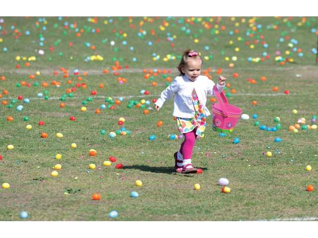 Samanta Van Loo, 2, runs through a field of eggs before the start of the egg hunt for children up to age 3.