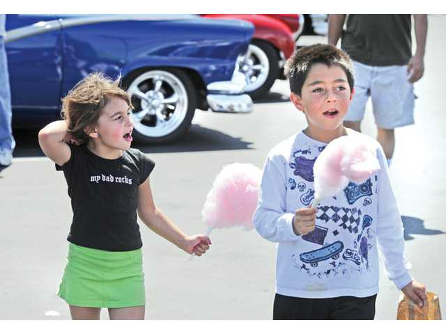 Bella Giglio, 5, left, and brother Kai, 8, walk among the classic cars on display as they sell cotton candy at the Arakaki Family Fundraiser and Classic Car Show held in the Albertsons parking lot in Saugus on April 16.
