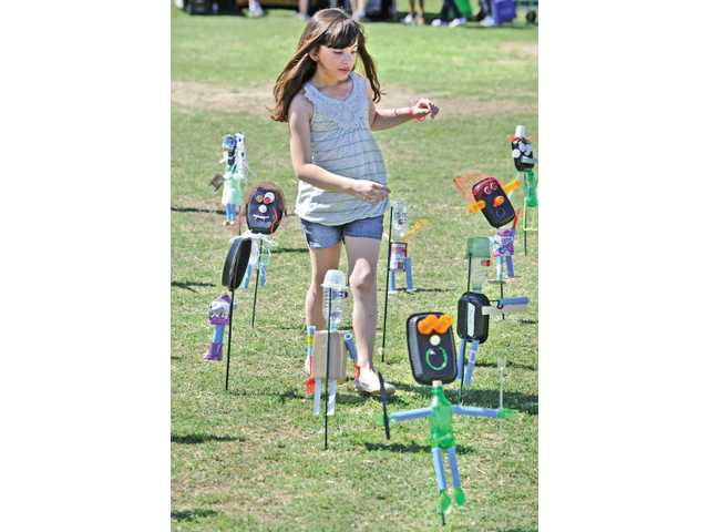 Amira Mahaluf, 6, of Valencia, walks through a display of recycled materials created by Cedarcreek Elementary School students at the City of Santa Clarita Earth Arbor Day Festival event held at Central Park in Saugus on April 16.