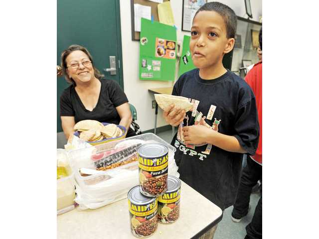 Fifth-grader Mark Awad, 10, right, eats pita bread filled with fava beans as Nadia Boktor looks on at the Egyptian booth in a multicultural-day event at Leona Cox Community School in Canyon Country on Tuesday.