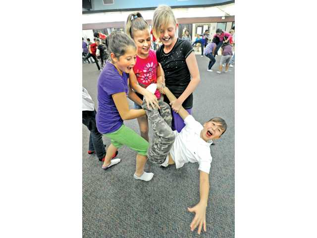 "Fifth-graders, from left, Victoria Dietz, Amanda Doucette and Hannah Legler hold onto Mack Bailey as they practice the ""balance study"" portion of their final performance of Lula Washington Dance Theater's 12-week class at Live Oak Elementary School in Castaic on Wednesday."