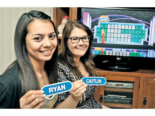 "Ryan Carter, 15, left, and Caitlin Dugger, 16, of Saugus, hold their nametags in front of the first ""Wheel"" puzzle they solved."