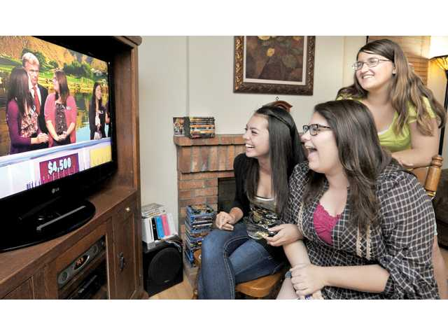 "Rebecca Dugger, 14, above right, joins her sister Caitlin, below right, and Ryan Carter as they watch themselves on ""Wheel of Fortune,"" which aired on April 20. A viewing party was held at Dugger's home in Saugus."
