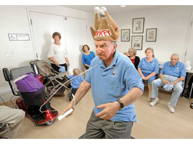 "Bernie Katz wears a ""turkey"" hat, indicating that he got three strikes in a row, as he bowls using the Wii controller at the SCV Senior Center on Tuesday."