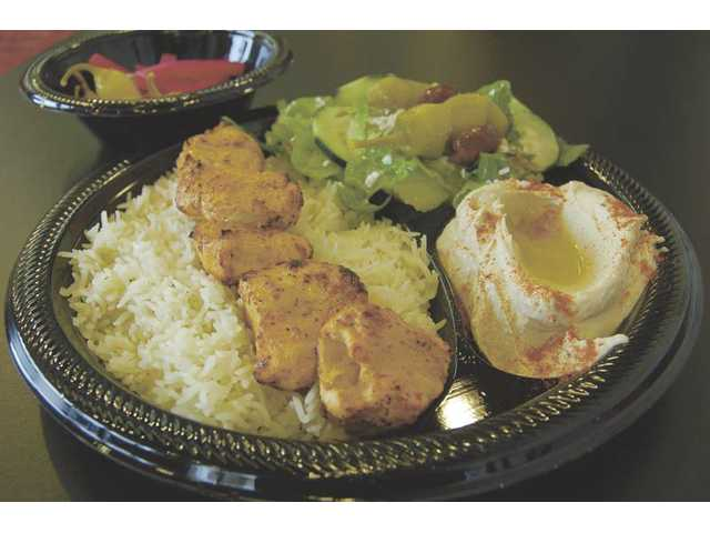 A chicken kabob plate ($8.99) features tender chicken breast chunks and your choice of two sides, including French fries, salad, rice and hummus.