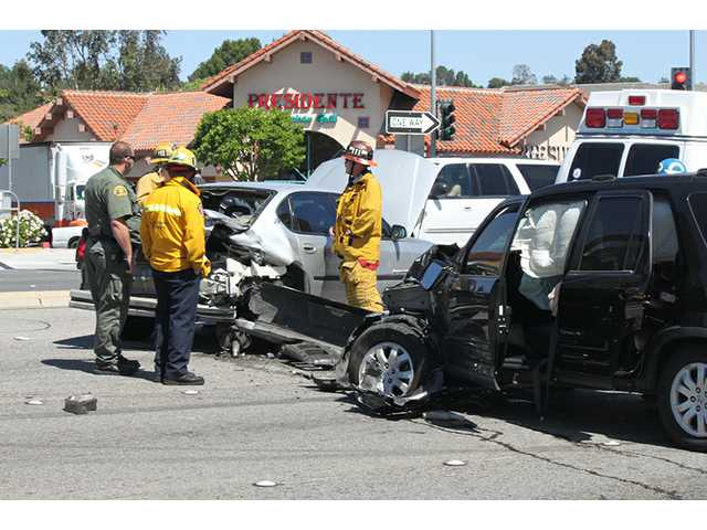 Los Angeles County Fire Department officials examine the site of a noninjury crash near the intersection of Bouquet Canyon Road and Espuella Drive in Saugus on Friday morning.