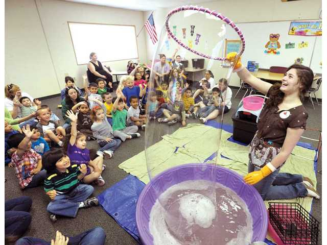 Krista Taylor, right, creates bubbles for 32 of special day-class preschoolers. Six classes were entertained as they learned about counting, shapes and colors through the use of multisized bubbles as a fun learning tool sponsored by the Leona Cox parent teacher association on Friday.