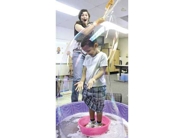 Krista Taylor, top, of Fun and Discovery Entertainment creates a huge bubble over Josh Jiru, 4, a preschool student in one of six special day class at Leona Cox Community School in Canyon Country on Friday.