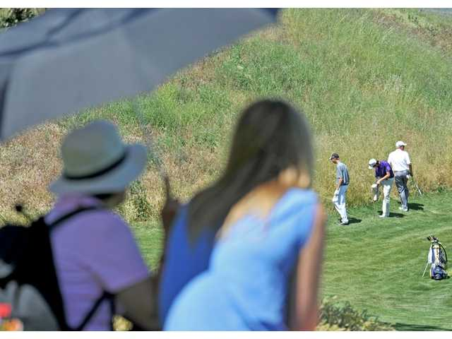 Elbie Flores, 60, of Castaic, left, and Kendall Dusenberry, 16, of Santa Clarita, watch under the shade as Saugus' Zack Leonard, Valencia's Jonathan Chang and West Ranch's J.J. Holen look for a lost ball near the fourth hole during the second round of the Newhall Land Cup on Wednesday at TPC Valencia.