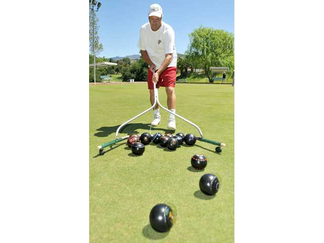 Keno Shaw, 53, rounds up bowls during a game of lawn bowling at Friendly Valley Country Club in Newhall on Tuesday.