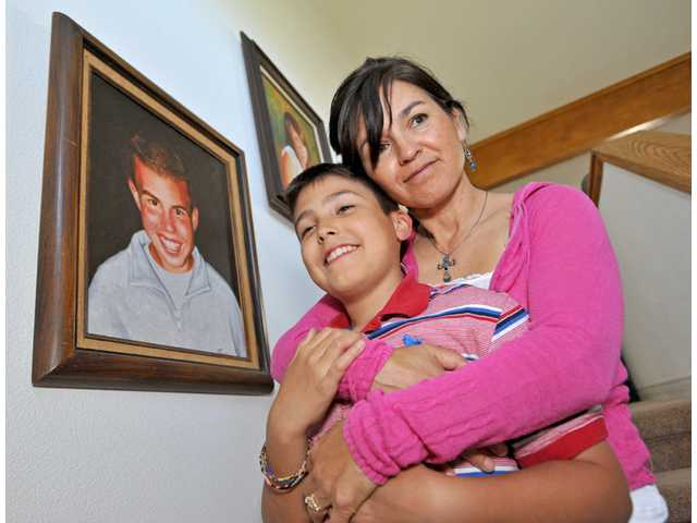 Lisa DeLong, right, holds her son Jacob, 11, in front of a portrait of Justin DeLong painted by Lisa's sister Lori Powers. Justin DeLong lost his battle with leukemia in 2000 at the age of 15. Jacob DeLong was diagnosed with leukemia at age 6.