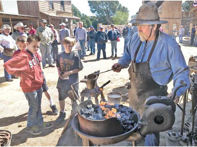 Talon Hudson, 10, left, and brothers Paul Veluzat, 10, and Noah, 9, behind, watch as blacksmith Bryan Jones creates a personalized horseshoe at the 2011 city of Santa Clarita Cowboy Festival at Melody Ranch Motion Picture Studio in Newhall on Saturday.