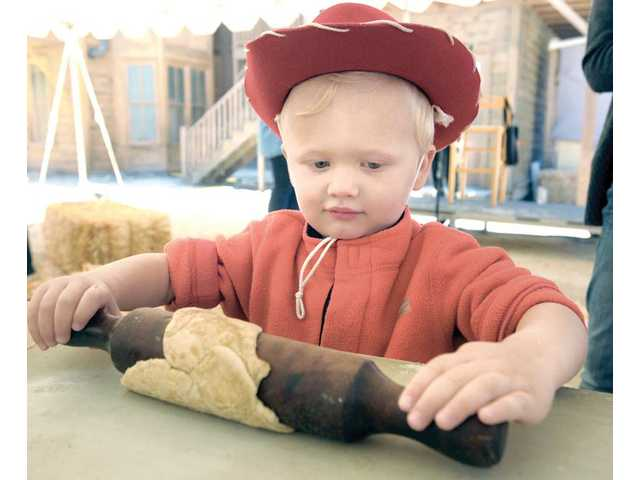 Malachi Biggers, 2, uses a rolling pin to discover how cowboys made biscuits at the Children's Corral at the Cowboy Festival.