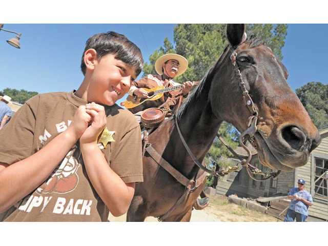 Eric Schultz, 10, left, of Valencia, is a little skittish with Gypsy the horse, as Mike Tcherkassky serenades visitors upon their entrance to the Cowboy Festival.
