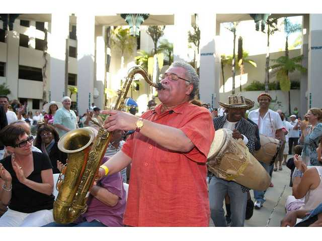 Saxophonist Justo Almario leads his band through the crowd at the Playboy jazz community concert on Sunday, May 1, in Beverly Hills.