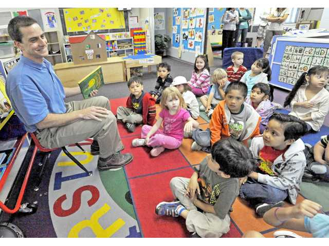 "Barry Gribbons, president of the Santa Clarita Valley Rotary Club, left, reads ""The Crunching Munching Caterpillar"" to preschoolers in the Saugus Union School District's state preschool program at Rio Vista Elementary School in Canyon Country on Monday."