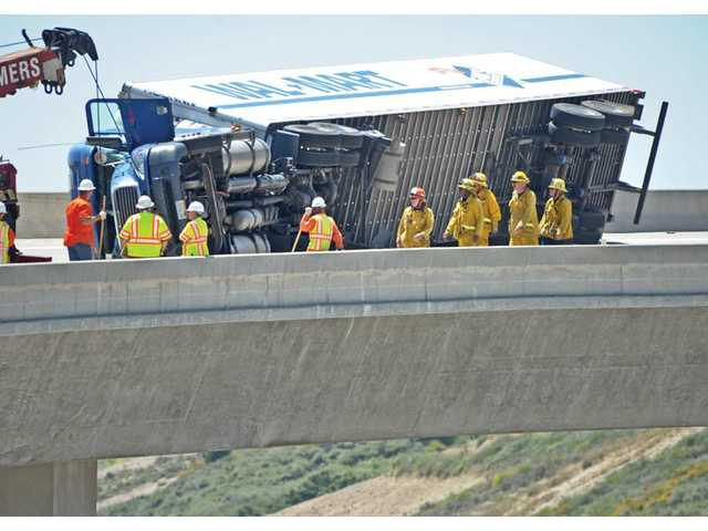 A Howard Sommers tow truck, Caltrans workers and firefighters prepare to pull the big-rig tractor trailer upright.