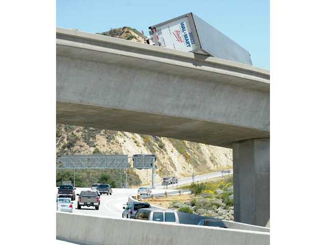 Cars traveling northbound on the Interstate 5 pass under a big-rig tractor trailer that overturned on the truck-lane transition overpass from the southbound I-5 to Highway 14 in Santa Clarita on Wednesday morning.