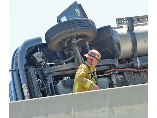 A firefighter from Fire Station 126 walks past a big-rig tractor trailer that overturned on the truck-lane transition overpass from the southbound Interstate 5 to the Highway 14 in Santa Clarita on Wednesday morning.