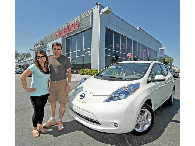 David Wang, of Agua Dulce, right, poses next to his new Nissan Leaf with his daughter Candice on the lot at Nissan of Valencia on Wednesday. Wang is the first customer in the Santa Clarita Valley to take delivery of the all-electric vehicle.