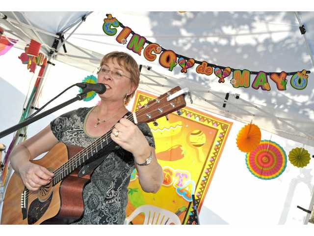 "Local singer-songwriter Trish Lester sings ""Bésame Mucho"" — often translated to ""Kiss Me Much"" — a 1940 song by Mexican songwriter Consuelo Velázquez, at the Taste of Cinco de Mayo in Old Town Newhall on Thursday"