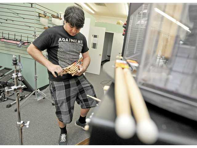 David Green, drummer of the group Moonraker, packs up drumsticks at World Music in Newhall on Thursday. Green had worked in sales at the store for four years.